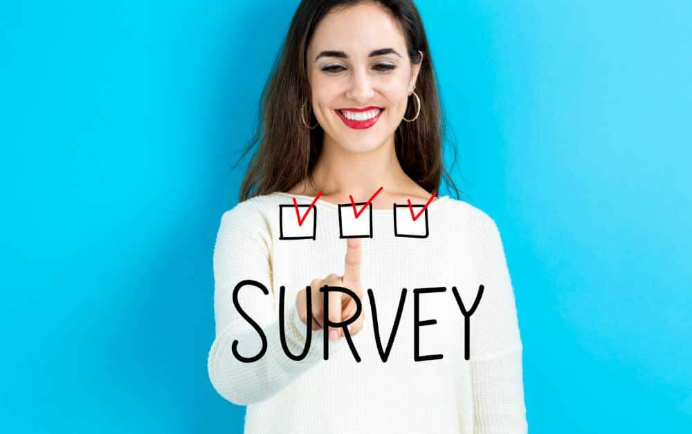 """Woman ticking a checkmark on a screen with the text """"Survey"""" written on it. Featured image for a blog post about surveys that pay through Paypal."""