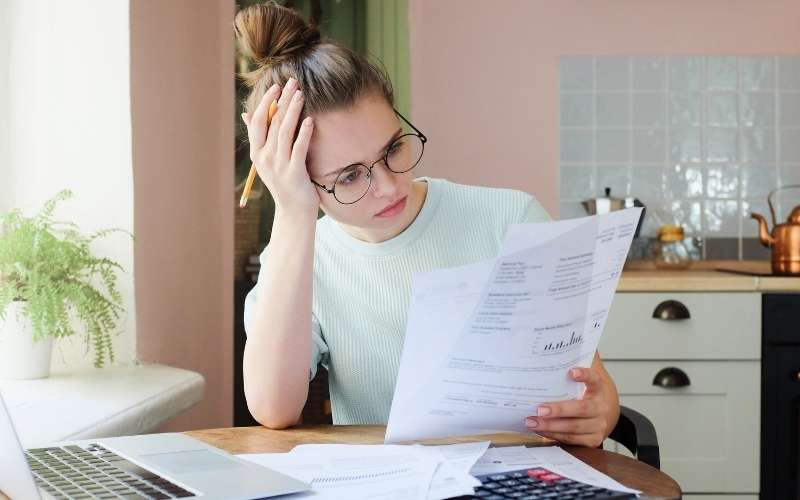 Woman with head in hands looking at bank statement in blog post about inspirational debt quotes