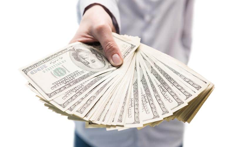 Hand holding 100 US Dollar notes in article about money affirmations